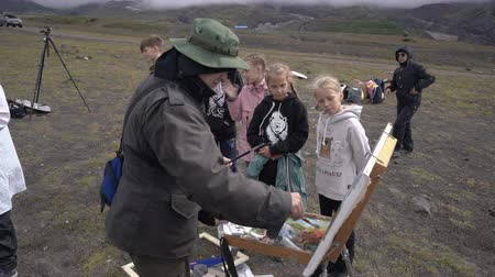 Group of children - boys and girls are looking professional creative artist painting on canvas mountain landscape in autumn. Avacha Volcano, Kamchatka Peninsula, Russian Far East - August 30, 2019.