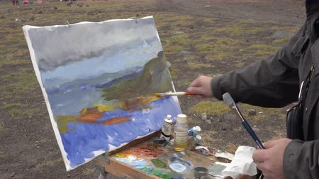 Creative painter draws brush oil paints on canvas mountains landscape, standing in open air in tundra during autumn gloomy overcast weather. Avacha Volcano, Kamchatka Peninsula, Russia - Aug 30, 2019