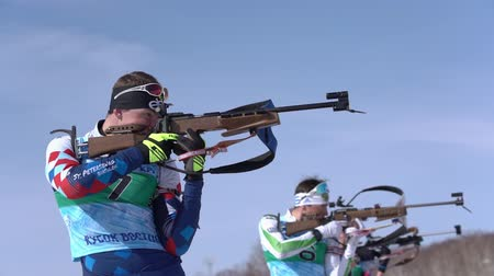 biathlete : Junior biathlon competitions East of Cup. Sportsman biathlete aiming, rifle shooting and reloading in standing position. Biathlete Roduner Dionis in shooting range. Kamchatka, Russia - April 14, 2019.