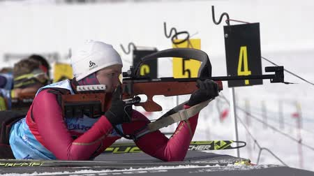 Sportswoman biathlete aiming, rifle shooting in prone position. Biathlete Andreeva Victoriya in shooting range. Junior biathlon competitions East of Cup. Kamchatka Peninsula, Russia - April 14, 2019