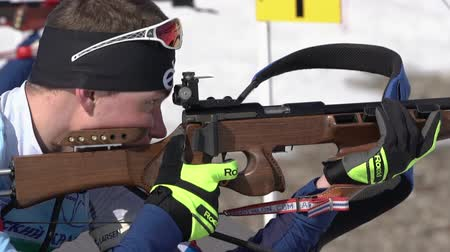 Biathlete aiming, rifle shooting, reloading rifle in prone position. Sportsman biathlete Roduner Dionis in shooting range. Junior biathlon competitions East of Cup. Kamchatka, Russia - April 14, 2019