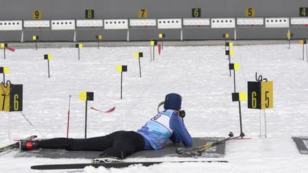 Sportsman biathlete aiming, rifle shooting, reloading rifle in prone position. Biathlete Taranov Anton in shooting range. Junior biathlon competitions East of Cup. Kamchatka, Russia - April 13, 2019. Стоковые видеозаписи