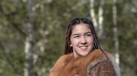 Portrait pretty girl smiling and happy in traditional clothing aborigine people. Itelmens national ritual festival thanksgiving nature Alhalalalay. Kamchatka Peninsula, Russian Far East - Sep 14, 2019 Стоковые видеозаписи
