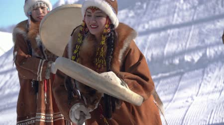 kutya : Indigenous female emotional dancing with tambourine in national winter clothing aborigine people. Kamchatka traditional Sled Dog Racing Competition Beringia. Kamchatka Peninsula, Russia - Feb 22, 2020