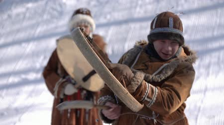 Indigenous male expression dancing with tambourine in national winter clothing aboriginal people. Kamchatka traditional Sled Dog Race Championship Beringia. Kamchatka Peninsula, Russia - Feb 22, 2020.