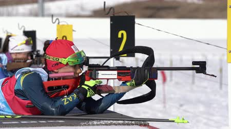 Sportswoman biathlete aiming, rifle shooting, reloading prone position. Biathlete Polina Yegorova Kazakhstan in shooting range. Junior biathlon competitions East Cup. Kamchatka, Russia - Apr 14, 2019. Стоковые видеозаписи