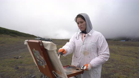 Girl creative painter draws brush oil paints on canvas autumn mountains landscape, standing in open air in tundra. Avacha Volcano, Kamchatka Peninsula, Russian Far East - August 30, 2019.