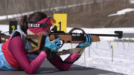 narciarz : Sportswoman biathlete aiming, rifle shooting in prone position. Biathlete Ivchenko Anastasia in shooting range. Junior biathlon competitions East of Cup. Kamchatka, Russian Far East - April 14, 2019