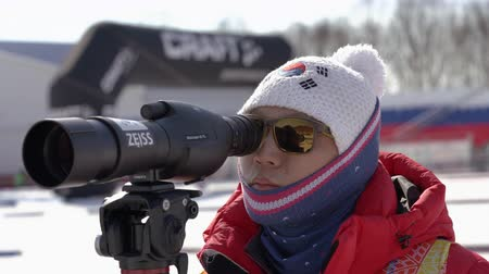 Trainer of South Korea biathlon team watches biathletes in monocle at shooting range of biathlon stadium. Junior biathlon competitions East of Cup. Kamchatka Peninsula, Russian Far East - Apr 14, 2019 Стоковые видеозаписи