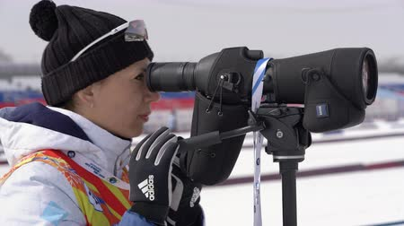 Russian trainer Aksenova Olesya watches biathletes in monocle during shooting at shooting range of biathlon stadium. Regional junior biathlon competitions East Cup. Kamchatka, Russia - April 13, 2019