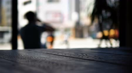 Footage of blurred background of man taking coffee and sitting at front of coffee shop and wood table on foreground and blurred on street in background.