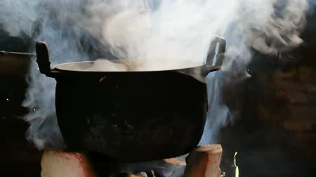 steaming basket : Black cooking pot pot with steam on earthen stove and firewood. Thai traditional wood burning stove. Stock Footage