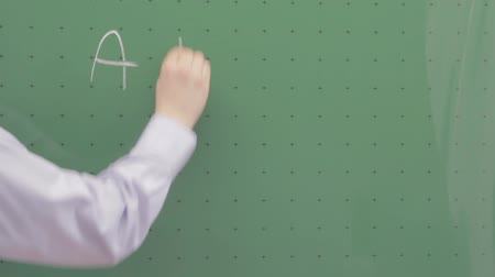 educar : Teacher writing ABC on a chalkboard Stock Footage