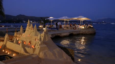 in : Puerto Pollensa Mallorca Spain: Sand castle with candles and people dining in the night