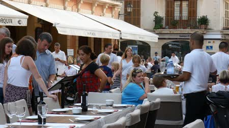 holiday makers : Alcudia Mallorca Spain: Holiday makers dining on the main square in the old town Stock Footage