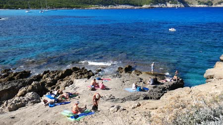 holiday makers : Cala Ratjada Mallorca Spain: Holiday makers sunbathing on the rocks