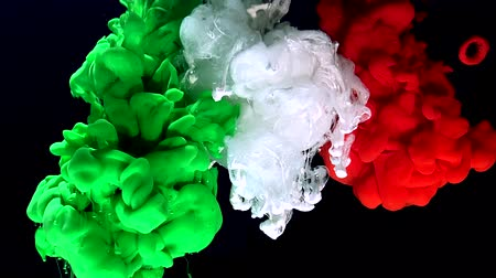 Flag of Italy from colored ink on a black background. Stylish abstract modern background. Green, white and red watercolor ink in water. A powerful explosion of colors. Cool trending screensaver.