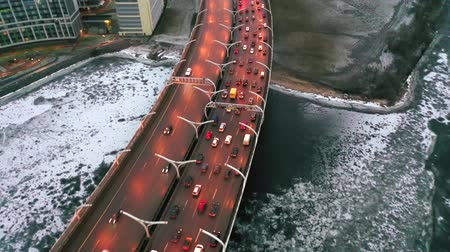 Aerial view of the highway in winter. The frozen Neva River, covered with ice. Cosmic cityscape in the evening. Drone flight over the city.