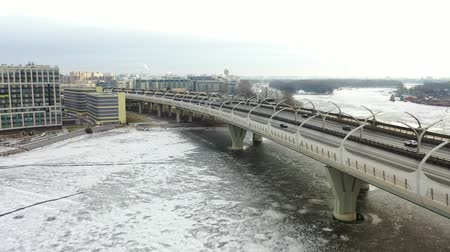 Aerial view of the highway in winter. The frozen Neva River, covered with ice. City landscape in the morning. Drone flight over the city.