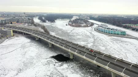 icy : Aerial view of the expressway in winter. The frozen Neva River, covered with ice. City landscape in the morning. Drone flight over the city.