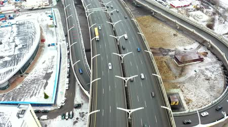 Road junction. Aerial view of the expressway in winter. City landscape in the morning. Drone flight over the city. Wideo