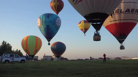 aventura : BELGOROD - AUG 4: Balloons fly in the sky with passengers over the green field, on Aug 4, 2018 in Belgorod, Russia