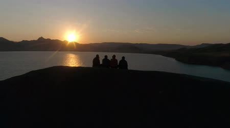 AERIAL. Four people at sunset sitting on a rock. Curling in the sea. Dostupné videozáznamy