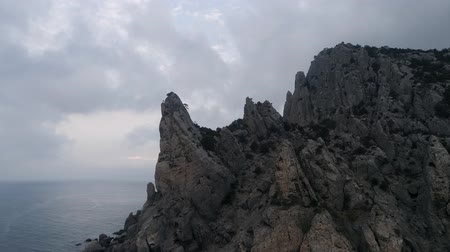 вулканический : AERIAL. Flying over a rock in the sea. Cloudy weather