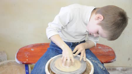 hrnčíř : elementary child shaping clay on pottery wheel