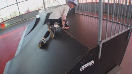 helmets : Child roller blading up and down trampolines in skating park with helmet and protective pads on. Childhood sports safety active lifestyle concept. Stock Footage