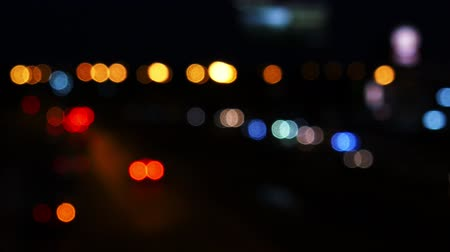 Moving bokeh circles from the lights of cars running on the city streets. City blur background.  Night traffic. Stock Footage