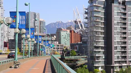 overlooks : VANCOUVER, BRITISH COLUMBIA,CANADA - CIRCA May 2012 :people cycling on cambie bridge - mountains