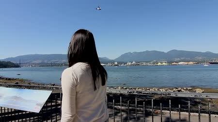 yanliŞ : VANCOUVER, BRITISH COLUMBIA,CANADA - CIRCA May 2012 :girl watches float plane from Stanley park