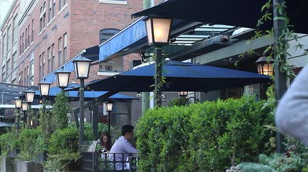 ing : VANCOUVER, BRITISH COLUMBIA,CANADA - CIRCA May 2012 :young blonde girl walking in yaletown - people dining