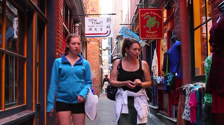парламент : VICTORIA, BRITISH COLUMBIA,CANADA - CIRCA May 2012 :2 angles - people walking in fan tan alley Стоковые видеозаписи