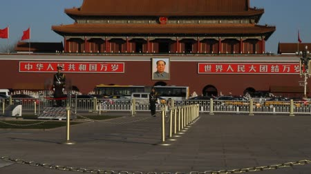 parede : a close shot that zooms out to a wide shot of a Tiananmen square guard across from Forbidden city