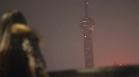 složení : Bund night scene - artistic shot of young stylish woman looking at the pearl tower with a full moon