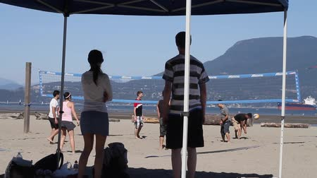 volleyball : VANCOUVER, BC ,CANADA - CIRCA September 2011 :outdoor summer volley - friends watch under tent Stock Footage