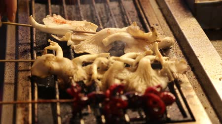 bintang : a live shot of some skewered mushrooms being cooked in the Bukit Bintang market Stock Footage