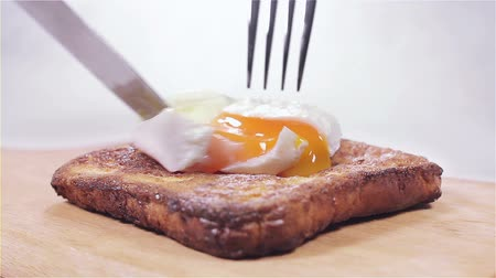 poached egg : Placing a poached egg on toast and slicing the the yolk.