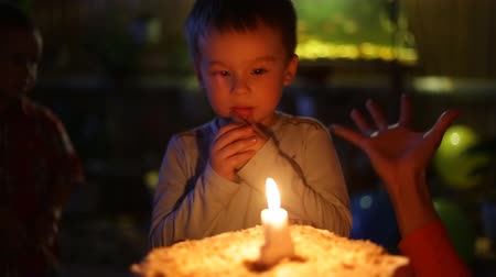 darbe : Closeup portrait of a little boy blows out the candles on the cake. Vertical image on a light background.