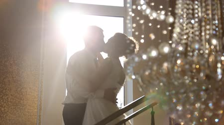 večer : silhouettes of the bride and groom on the background of the window