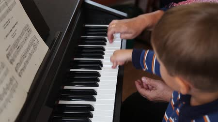 lesson : Boy learning how to the play piano with teacher Stock Footage