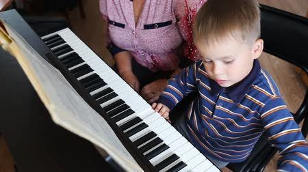 özel öğretmen : Boy learning how to the play piano with teacher Stok Video