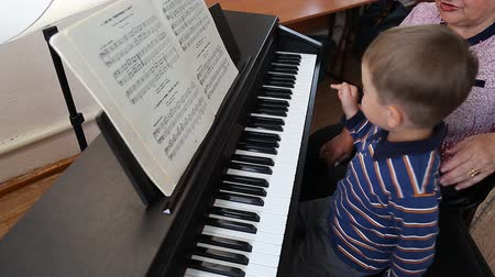 latino americana : Boy learning how to the play piano with teacher Vídeos