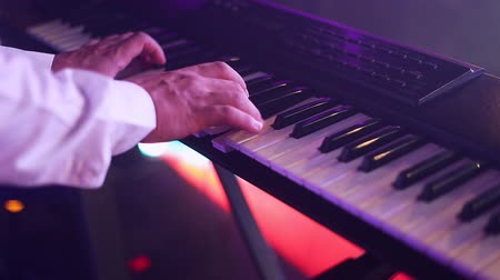 electric : hands of musician playing keyboard in concert with shallow depth of field, focus on right hand