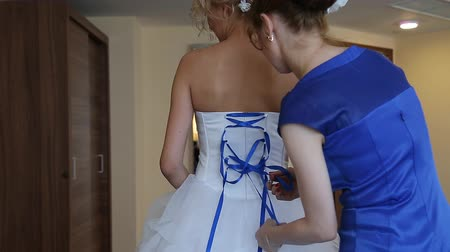 cerimônia : bridesmaid tying bow on wedding dress Vídeos