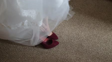 high heels : Bride dresses shoes before the wedding ceremony Stock Footage