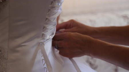 traditional ceremony : bridesmaid tying bow on wedding dress Stock Footage