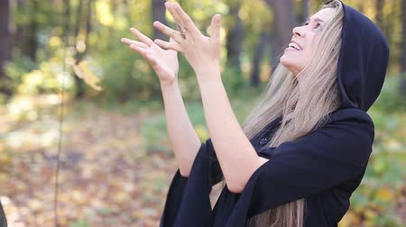 kostüm : beautiful witch with a pumpkin in autumn forest Stok Video